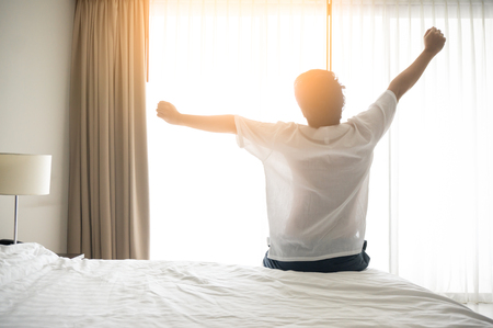 Man wake up and stretching in morning with sunlight Stockfoto