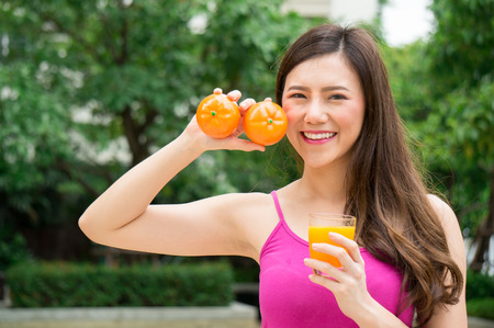 Asian healthy woman eat orange juice for health with smile