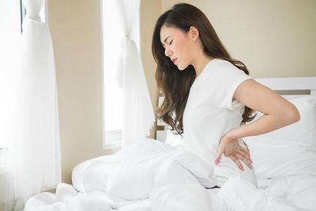 Une femme asiatique a mal au dos dans la chambre le matin à cause d'un problème de sommeil Banque d'images