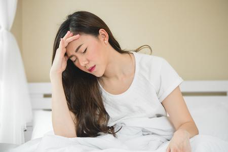 La mujer asiática tiene dolor de cabeza en el dormitorio por la mañana porque tiene problemas para dormir. Foto de archivo