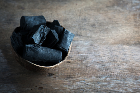 Charcoal in coconut shell for spa on the wood background for advertisement Reklamní fotografie