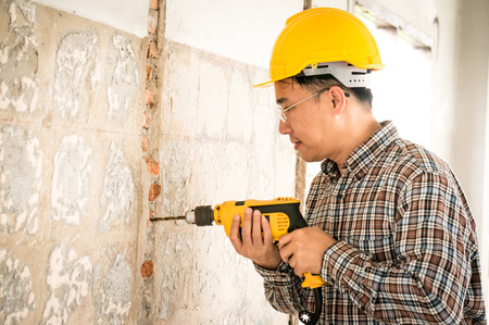 Foreman wearing helmet drilling wal by drill Stock Photo