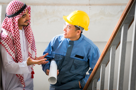 Arab businessman discuss with foreman wearing safety helmet and holding drawing in hand 스톡 콘텐츠