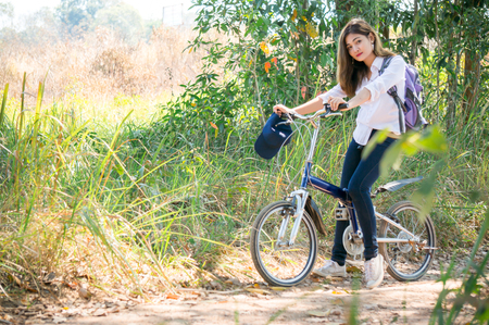 A young woman / traveller in white shirt with smile riding bicycle in national park with green trees 스톡 콘텐츠