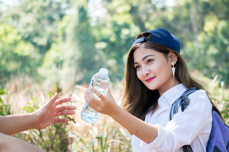 Asian woman send water bottle to friend among national park on forest background