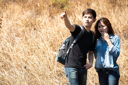 Asian travelers as couple pointing to target in autumn forest