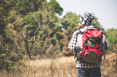 Traveler looking to map on the way in forest 스톡 콘텐츠