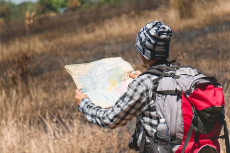 Asian backpacker hold map in forest 스톡 콘텐츠