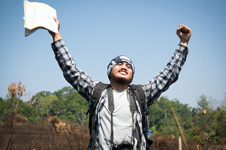 Asian traveler holding map and camera feeling relax in national park