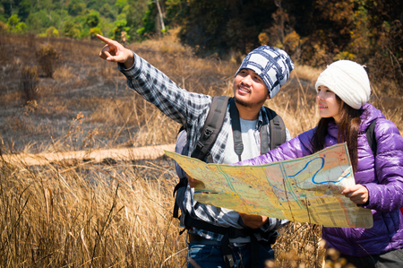 Asian travelers holding map and find target in forest 스톡 콘텐츠