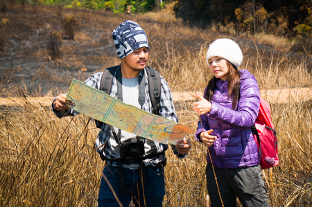 Asian traveler holding map and thumb-up in forest