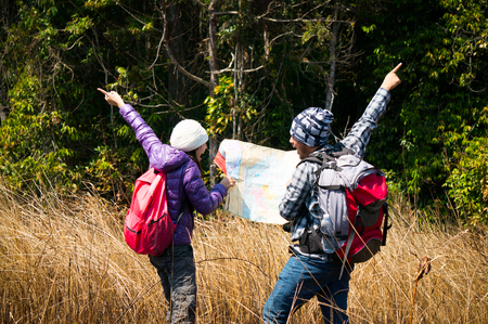 Asian travelers holding map and argue in forest