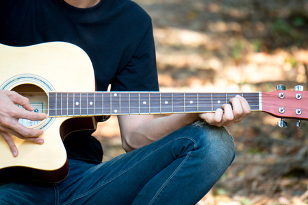 Close up a man playing guitar in park with hand on cord