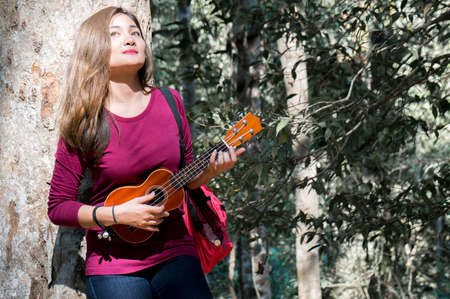 Asian woman feeling relax playing ukulele in park on green nature background