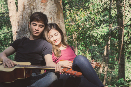 Asian couple traveler with guitar and ukulele relax in forest together