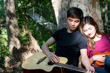 Asian couple with guitar and ukulele is sleeping in forest together 스톡 콘텐츠