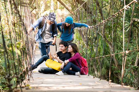 Asian traveler group discuss in forest