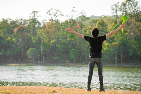 A young man playing a green windmill with freedom feeling on green forest background