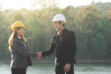 Two engineers wearing formal suit and safety helmet shake hands on riverside among sunlight in national park