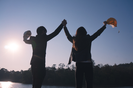 Two engineers raising hand and holding safety helmet in hand feeling success in silhouette