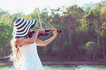 Violinist playing violin on riverside and forest with relaxation 스톡 콘텐츠