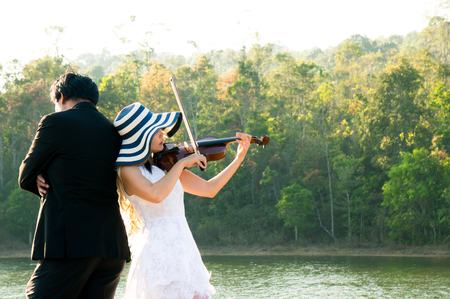 A woman / violinist wearing white dress and hat playing violin on riverside among sunlight feeling freedom
