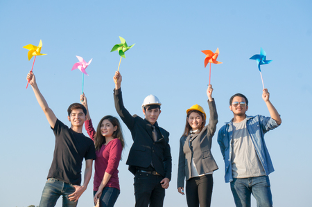 New generation people (engineer, musician, couple) raising hand and holding colorful windmill / wind turbine in hand on sky background in save earth concept 스톡 콘텐츠