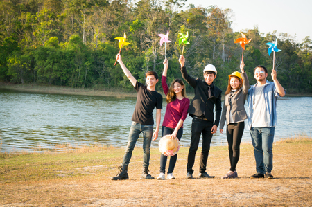 New generation Asian people holding paper windmill in hand in save the world concept for future in nation park on green forest and river background