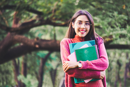 Asian woman with books in park for education concept