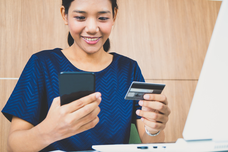 Asian woman online shopping via smart phone by credit card 스톡 콘텐츠 - 121328843