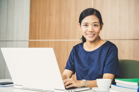 Asian woman working on laptop on desk with coffee in morning 스톡 콘텐츠