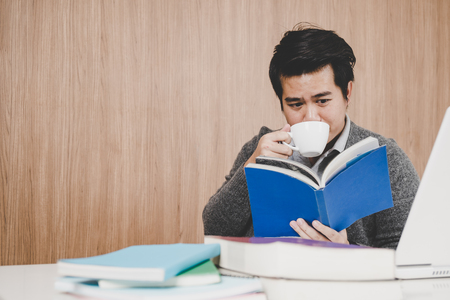 Asian man reading book with coffee 스톡 콘텐츠 - 121328847