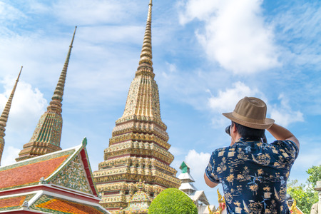 Asian traveler shoots photo of Wat Pho temple in Thailand in vacation period