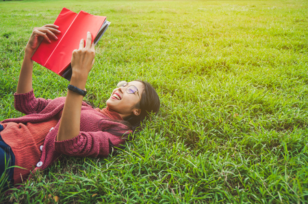 Asian woman with books in park for education concept 스톡 콘텐츠 - 120134860