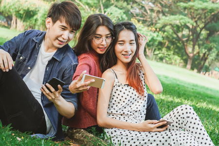 Asian student selfies in park with friend
