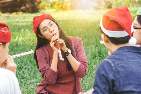Asian woman and friend celebrate Christmas holiday in park