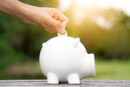 Woman save money with white piggy for investment
