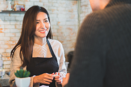 Asian woman hand over coffee cup to customer