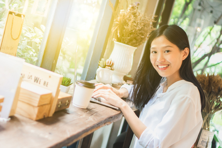 Asian woman working on labtop in coffee shop 스톡 콘텐츠 - 121329037