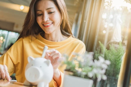 Asian woman saving money and dropping coin to piggy