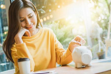 Asiatische Frau, die Geld spart und Münze auf das Schweinchen fallen lässt