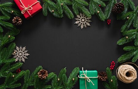 Christmas background with decoration, red and green gifts, snow flake ,berries, pine branches and cones, rope on black background with center copy space 스톡 콘텐츠 - 131979909