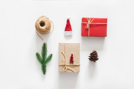 Christmas composition. Christmas gifts, pine branches, pine cone, berries, rope, toys on white background. Flat lay, top view.