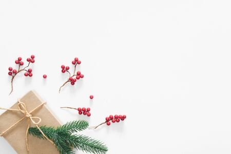 Christmas gift on white background with pine branches, berries and rope. Flat lay, top view, copy space