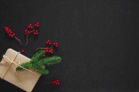 Christmas gift on black background with pine branches, berries and rope. Flat lay, top view, copy space 免版税图像