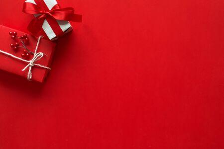 Kerstcadeaus presenteert op rode achtergrond. Eenvoudige, klassieke rood-wit verpakte geschenkdozen met strikken en feestelijke decoraties voor de feestdagen Stockfoto