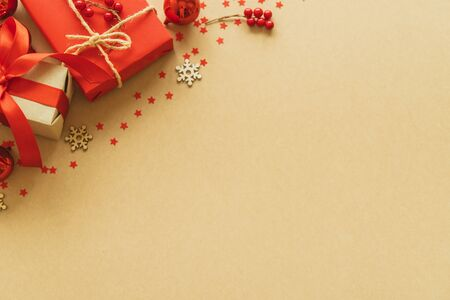 Christmas gifts on paper background with decoration, berries, star, snow flake and copy space. Flat lay, top view