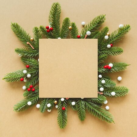 Christmas Flame made from red berries and green branches with snow on paper background. Flat lay, top view.