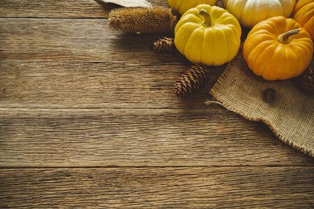 Autumn Thanksgiving day background from fallen leaves and fruits, pumpkin with vintage place setting on old wooden table. Thanksgiving day concept 스톡 콘텐츠