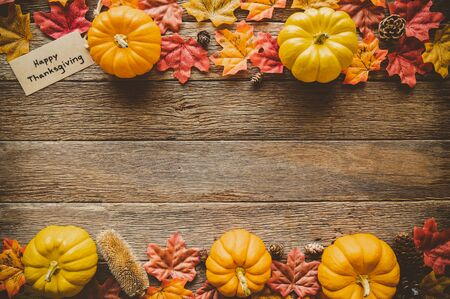 Autumn Thanksgiving day background from fallen leaves and fruits, pumpkin with vintage place setting on old wooden table. Thanksgiving day concept 免版税图像